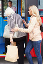 Woman helping senior woman to board bus holding arm with driver in background Stock Photography