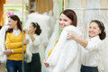 Woman helps the bride in choosing fur cape at shop of wedding fashion focus on girl Stock Images