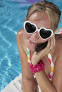 Woman on her Cellphone by the Pool Stock Photography