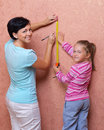 Woman with her daughter doing home repair Stock Images
