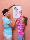 Woman and her daughter hanging up photo Royalty Free Stock Photo