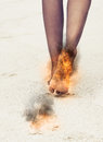 Woman with her feet aflame and scorch marks burning black on legs over a textured neutral background reflection Royalty Free Stock Photo