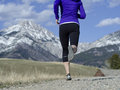 Woman in her fifties running in montana a down a dirt road under a beautiful blue sky with the mountains the background Stock Photo