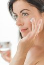 Woman in her forties applying cream portrait of a beautiful mature lady preventing wrinkles by using luxurious face lotion Stock Photo