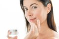 Woman in her forties applying face cream portrait of a beautiful mature lady preventing wrinkles by using luxurious lotion Royalty Free Stock Photography