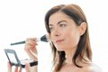 Woman in her forties applying makeup portrait of a beautiful mature lady using professional brush to apply powder on cheekbones Stock Image