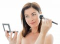 Woman in her forties applying makeup portrait of a beautiful mature lady using professional brushes to apply powder on cheekbones Stock Photo