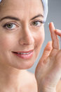 Woman in her forties inserting contact lenses attractive mature lady putting on eyes Royalty Free Stock Images