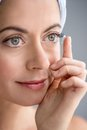 Woman in her forties inserting contact lenses close up of an attractive mature lady putting on green eyes Stock Images