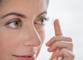 Woman in her forties inserting contact lenses close up of an attractive mature lady putting on green eyes Royalty Free Stock Photography