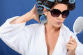 Woman with her hair in rollers holding a brush and wearing sunglasses Royalty Free Stock Photos