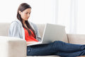 A woman with her laptop on the couch with legs outstretched Stock Photo