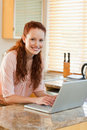 Woman with her laptop next to the kitchen counter Stock Photo