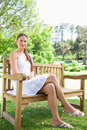Woman with her legs crossed sitting on a park bench Stock Photography