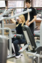 Woman with her personal fitness trainer in the gym exercise weight train Stock Image