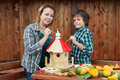 Woman and her son painting a bird house with vivid colors Stock Photos