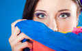 Woman hides her face with shawl on blue young make up eyes multicolored veiled girl background Stock Images
