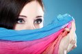 Woman hides her face with shawl young make up on eyes multicolored blue background Stock Image