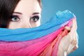 Woman hides her face with shawl young make up on eyes multicolored blue background Stock Photo