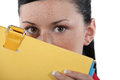 Woman hiding behind folder shy Royalty Free Stock Photo