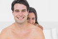Woman hiding behind shirtless partner in bed Royalty Free Stock Photo