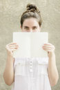 Woman hiding half of her face behind empty white paper notebook close up with green eyes wearing sleeveless blouse and pencil in Royalty Free Stock Photos