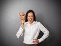 Woman hiding her anger behind the mask young businesswoman of indifferent mood Stock Photo