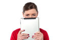 Woman hiding her face with tablet device lady touch pad against white Royalty Free Stock Images