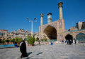 Woman in hijab rushes from Imam Khomeini Mosque built in early 18th with two minarets. Royalty Free Stock Photo
