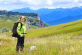 Woman hiker with backpack standing outdoor on green valley grass and mountains rocks on background summer day Stock Photo