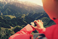 Woman hiker checking the altimeter on sports watch at mountain peak Royalty Free Stock Photo
