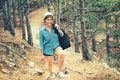 Woman hiker going on path, mountains with backpack. Concept of traveling and trekking on coastline Royalty Free Stock Photo
