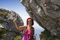Woman hiker high in the the mountain showing ok sign pretty middle aged with her hand under big rock with signpost mountains Royalty Free Stock Photo