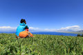 woman hiker sitting on a grass mountain top with first person perspective view Royalty Free Stock Photo