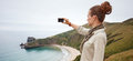 Woman hiker taking photo in front of ocean view landscape Royalty Free Stock Photo