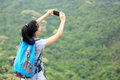 Woman hiker taking photo with smart phone stand mountain peak Royalty Free Stock Images