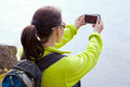 Woman hiker taking a photo by smartphone Royalty Free Stock Images