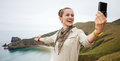 Woman hiker taking selfie in front of ocean view landscape Royalty Free Stock Photo