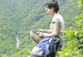 Woman hiker use tablet young asian sit mountain peak Royalty Free Stock Photo