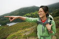 Woman hiking in lake district an east asian pointing the direction cumbria uk Stock Images