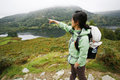 Woman hiking in lake district an east asian pointing the direction cumbria uk Stock Photography