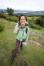 Woman hiking in lake district smiling east asian cumbria uk windermere the far distance Stock Images