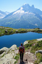 Woman hiking in the mountains on a tourist track with backpack walking beautiful landscape blue lake Stock Image