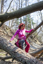 Woman hiking over a fallen tree trunks cute middle aged Stock Photography
