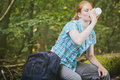 Woman on a hiking trip drinking water female hiker sits tree log next to backpack and drinks from white bottle Royalty Free Stock Image