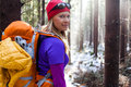 Woman hiking in winter forest white recreation and healthy lifestyle outdoors nature beauty blond looking at camera on sunset Stock Photo