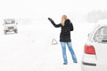 Woman hitchhiking having trouble with car snow Royalty Free Stock Image