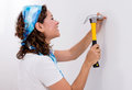 Woman hitting a nail casual in wall with hammer Royalty Free Stock Photos