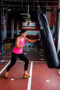 Woman hitting the punching bag a in a sport area Stock Photography