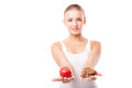Woman holding apple and chocolate isolated doubtful an trying to decide which one to eat on white background Royalty Free Stock Photography